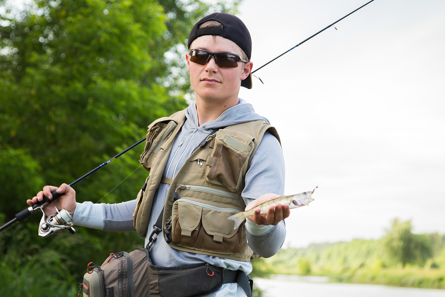 d7cf99c8426 Fisherman in professional gear on the river bank. Polarized Fishing Glasses