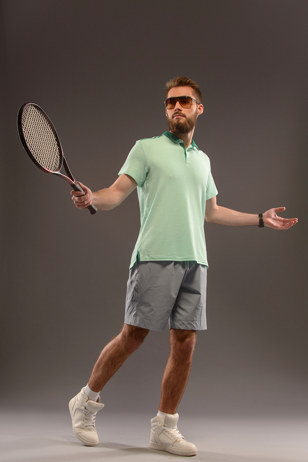 add493215df Handsome young man in polo shirt holding tennis racket - Sunglasses ...